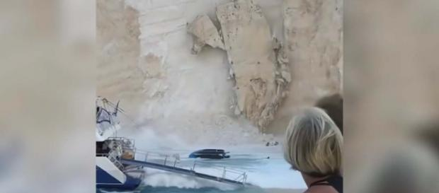 The moment tons of rock crashed down on a busy beach in Greece. [Image Guardian News/YouTube]