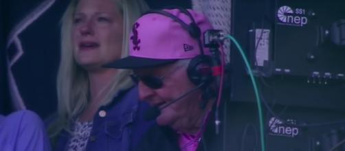 'Hawk' Harrelson calling a game between the Chicago Cubs and Chicago White Sox with his family near. [Image Source: MLB - YouTube]