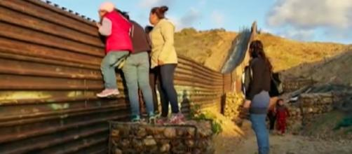 Migrant families continue to spill over Tijuana border fence, head to U.S. [Image source/Global News YouTube video]
