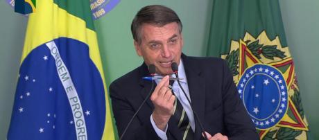 Bolsonaro mostrando a caneta que utilizou para assinar o decreto. (Reprodução / NBR)
