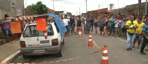 População observa carro em que funcionários da Cemar foram mortos a tiros (Reprodução/TV Mirante)