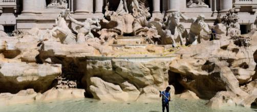 Os turistas visitam a fonte e jogam moedas pedindo por desejos. (Foto: ALBERTO PIZZOLI/AFP)
