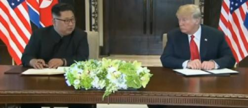 Donald Trump and Kim Jong-un sign document after summit. [Image source/ABC News (Australia) YouTube video]