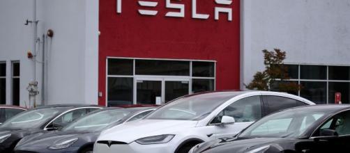 Des Tesla garées devant un batiment Tesla