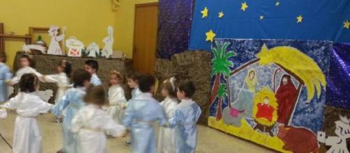 Bambini che danzano e cantano davanti al Presepe