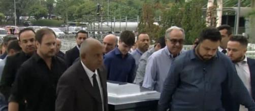 De azul, filho mais velho de Gugu ajuda a carregar caixão do pai. (Reprodução/Record TV)