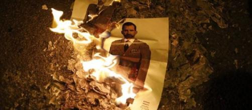 Dos imágenes de Felipe VI arden en la Avenida Diagonal de Barcelona. / ALBERT GARCIA
