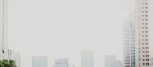 Carros e cidade com nuvem de poluição