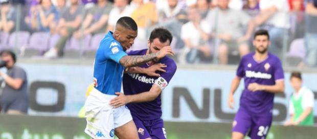 Allan e l'ex capitano della Fiorentina, Badelj, lottano per un pallone a centrocampo.