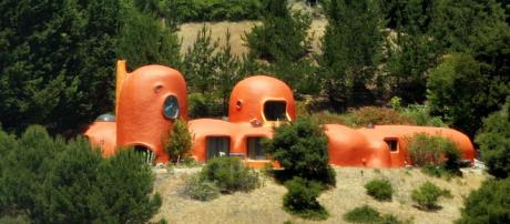 The Flintstone House, pictured here, has had a herd of massive dinosaurs added to it on on an astro turf lawn. [Image Sergei Krupnov/Wikimedia]