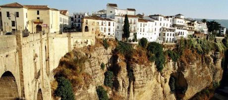 Houses cling to the cliffs alongside the New Bridge and the El Tajo Gorge in Ronda, Spain. [Image TUI/Wikimedia]