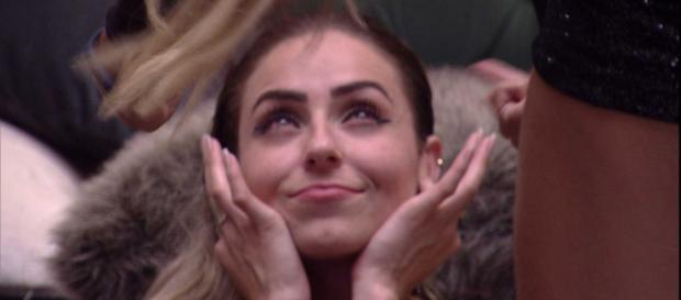 Paula sorri e tampa os ouvidos enquanto Hariany grita. (Reprodução/TV Globo)