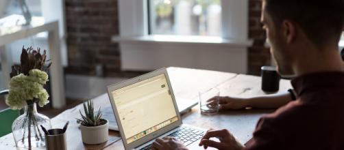 Jeune homme travaillant sur ordinateur dans un openspace