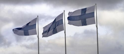 Three Finnish flags flying on poles. [Image via LTapsaH - Pixabay]
