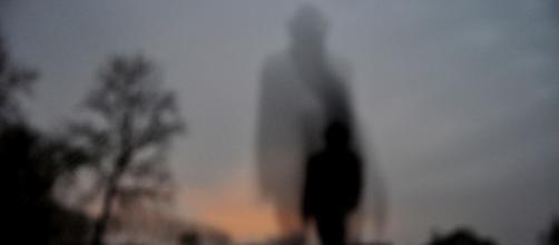 Una sombra femenina vigilando a un niño
