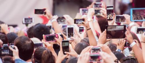 Pubblico con telefoni e tablet durante un concerto