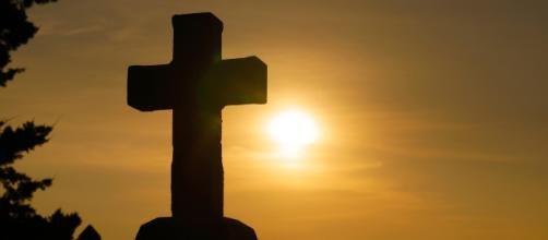 A Christian Cross with the sun in the background. [Image via sspiehs3 - Pixabay]