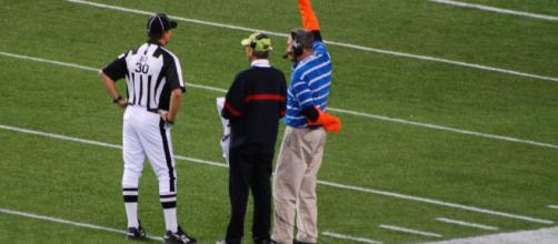 A ref is seen talking to television coordinators on the sidelines. [image source: Michael Holley- Wikimedia Commons]