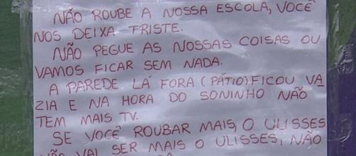 Crianças escrevem cartaz após sequência de furtos em escola. (Reprodução/ TV Globo)