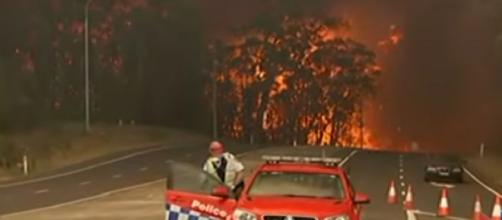 Raging Australian bushfire force residents to water's edge. [Image source/Global News YouTube video]