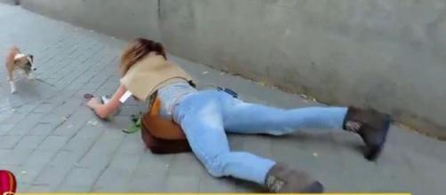 María Patiño tumbada en el suelo, mientras paseaba a su perro y grababa para su programa