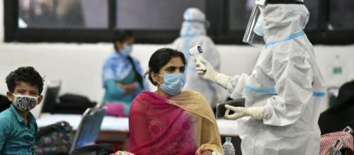 Un sanitario toma la temperatura a una mujer en India