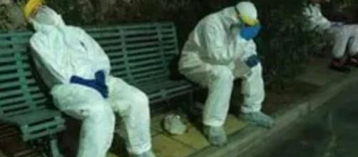 Coronavirus, l'immagine destinata a diventare il simbolo della seconda ondata: operatori sanitari stremati fuori dall'ospedale di Cagliari.