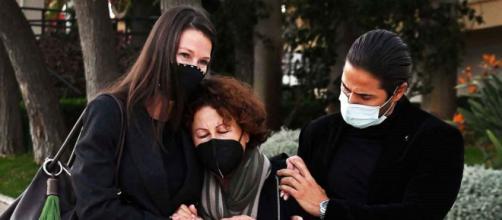 Esther Doña sostiene a su madre acompañada por su hermano en el funeral de su padre