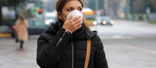 Une jeune femme se protégeant du coronavirus avec un masque - capture d'écran Facebook