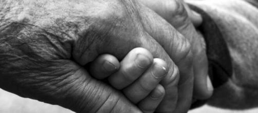 Una abuela y su nieto dándose la mano.