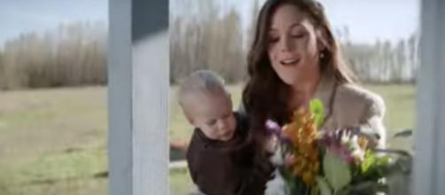 """Elizabeth (Erin Krakow) of """"When Calls the Heart"""" is flattered by the gift at her door in a Season 7 peek .[Image source:HallmarkChannel-YouTube]"""