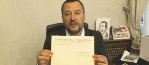 Matteo Salvini che, in passato, mostrava un avviso di garanzia durante una diretta Facebook.