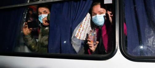 AP - Pasajeros evacuados de Wuhan miran por la ventana de un autobús afuera de Novi Sarzhany, Ucrania, el jueves 20 de febrero de 2020