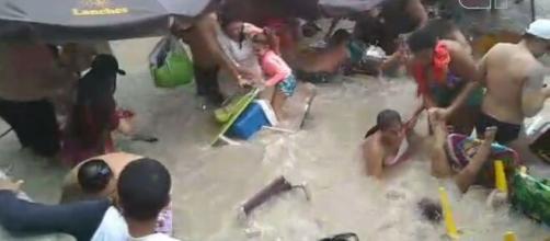 Banhistas tentam salvar pertences em meio à água que invadiu a areia. (Reprodução/Redes Sociais)