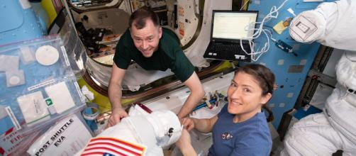 NASA astronauts Nick Hague and Christina Koch work on U.S. spacesuits. [Image source/NASA Wikimedia commons]