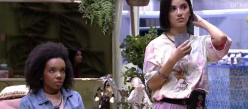 Manu e Thelma olham para telão e notam mudança. (Reprodução/TV Globo)