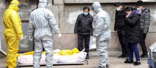 Un equipo de sanitarios junto a un cuerpo en Wuhan.