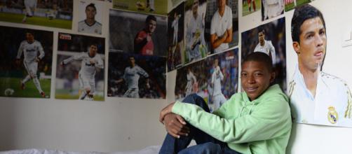 Kylian Mbappé dans sa chambre avec les posters de Cristiano Ronaldo.