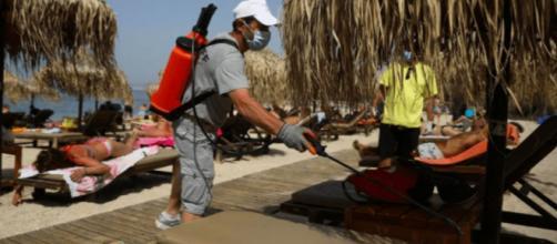 En Grecia, personal desinfecta las reposeras de las playas.