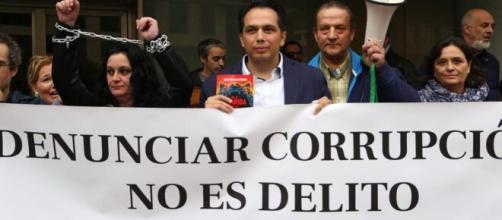 Roberto Macías (en el centro de la foto) sosteniendo una pancarta en una concentración anti-corrupción