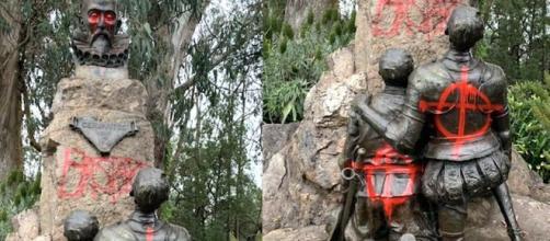 """La estatua de Cervantes vandalizada con la palabra """"bastardo"""" escrita en ella."""