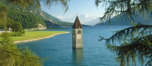 El campanario de la iglesia del siglo XIV de Santa Katharina emerge de las azules aguas del lago en Curon.