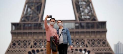 Due turisti scattano un selfie in piazza Trocadero, una zona non interessata dal provvedimento che entra in vigore il 10 agosto.