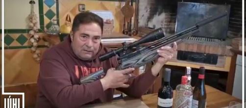 Un miembro de Vox convoca a un acto del partido empuñando un rifle.