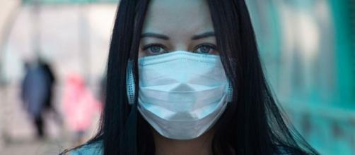 Mujer usando la mascarilla quirúrgica obligatoria Fuente Google Licencia Creative Commons
