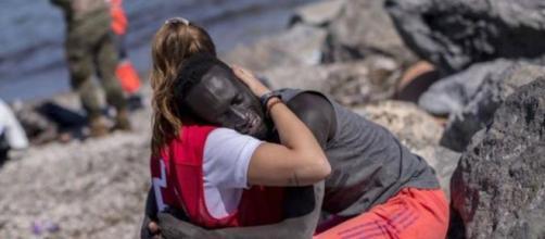 La joven voluntaria de la Cruz Roja, el migrante y un abrazo que es símbolo. (Twitter)