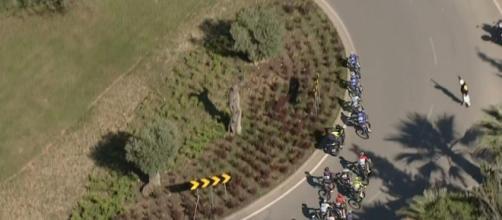 Una moto cerca di superare i corridori in una rotonda alla Volta Algarve.