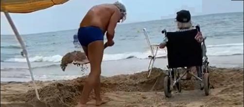 Un hombre saca la arena del camino para que su madre pueda acercarse al mar. (Facebook Manuel Lara Rosa)