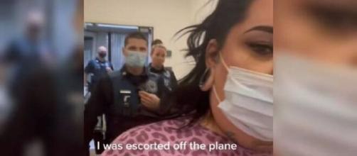 La mujer rapera Fat Trophy Wife, siendo escoltada por la policía a la salida del avión. (Tik Tok/ @fattrophywife)