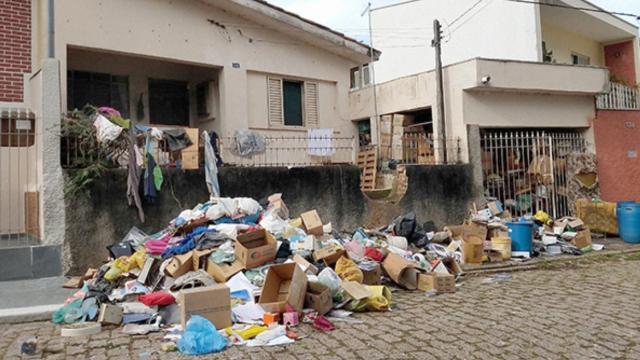 Mulher acumula lixo por mais de 20 anos e marido tem que quebrar muro para entrar em casa